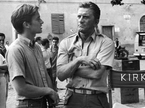 American actor Kirk Douglas (right) and his son American actor Michael Douglas on the set of the film, 'Cast a Giant Shadow,' directed by Melville Shavelson, Rome, Italy, 1965. Kirk had the starring role and Michael had a bit part. (Photo by Hulton Archive/Getty Images)