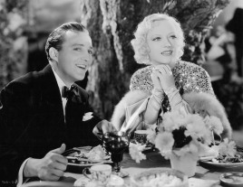 Bing Crosby and Marion Davies sit at table in a scene from the film 'Going Hollywood', 1933. (Photo by Metro-Goldwyn-Mayer/Getty Images)
