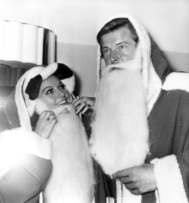 """Actors Luisa Mattioli and her husband Roger Moore don """"Father Christmas"""" costumes at the Variety Club of Great Britain's Christmas luncheon at the Savoy Hotel in London, Dec. 9, 1969. They are collecting gifts for sick and deprived children. (AP Photo/Bob Dear)"""